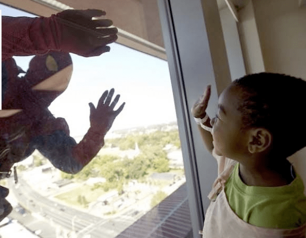 some window washers at children's hospitals surprise the kids by dressing up like superheroes
