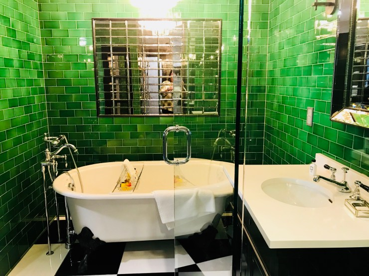 This emerald green bathroom has a large clawfoot tub in addition to a walk in shower with floating glass doors.