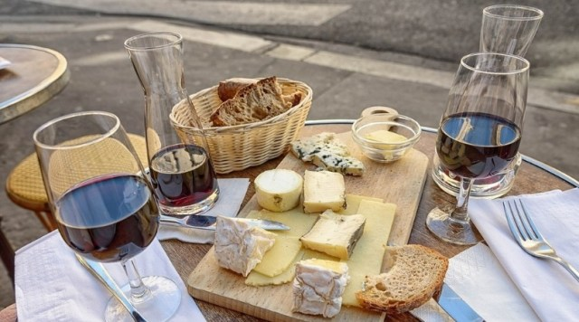 Image of outdoor cafe table with wine, cheese, and bread laid out.