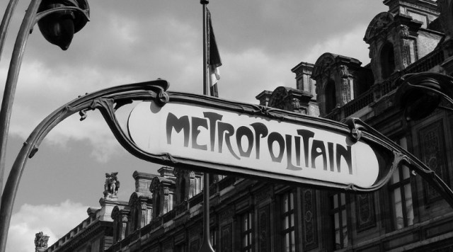 """Black and white photo of the Paris Metro's """"Metropolitain"""" signs with French buildings in the background"""