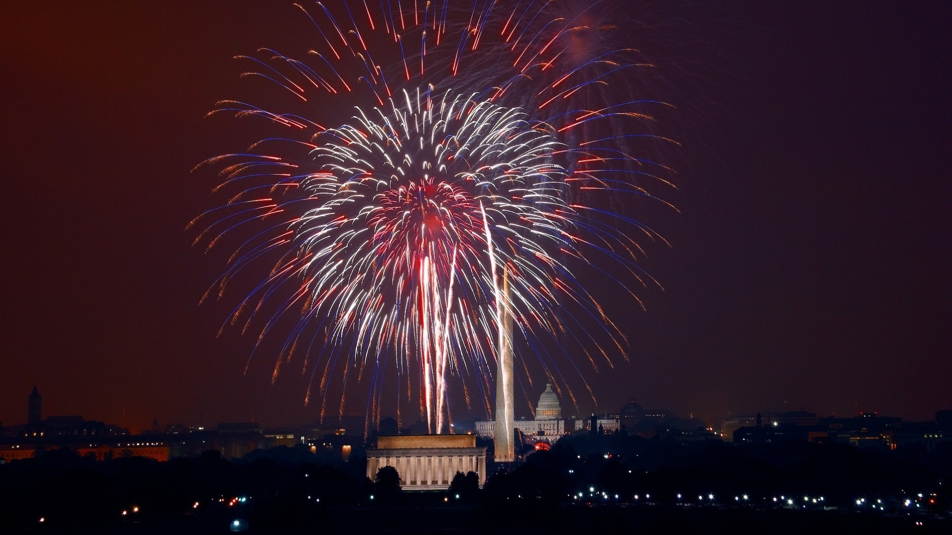 Fourth of July fireworks over the Lincoln Memorial with the Capitol in the background.