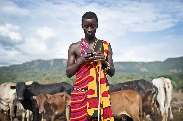 Isaac Mkalia, 20 years old, a teacher by profession is checking his mobile phone. Photo from http://www.oxfamblogs.org/eastafrica/?p=3615