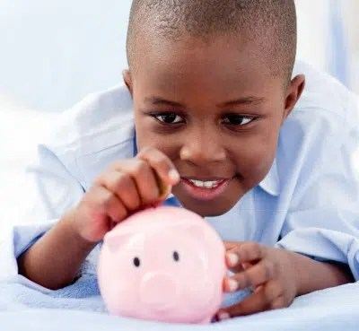 A child putting money in the piggybank. Image from http://fabulousandmoneysavvy.com/talking-with-your-children-about-finances/
