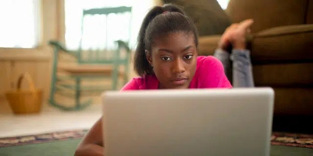 A teen on floor with laptop. Image from http://madamenoire.com/581061/protecting-your-child-online/