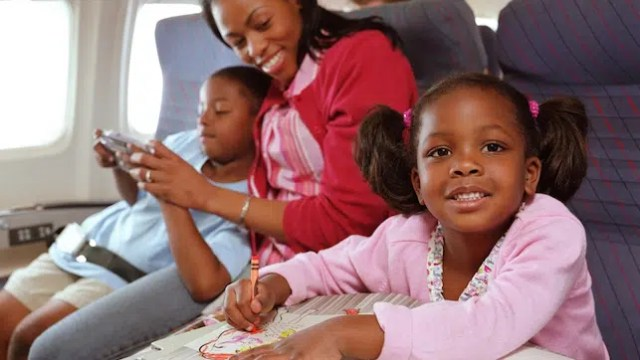 Family relaxing on aeroplane, girl (3-5) colouring, smiling. Image from http://www.womensforum.com/flying-with-kids.html
