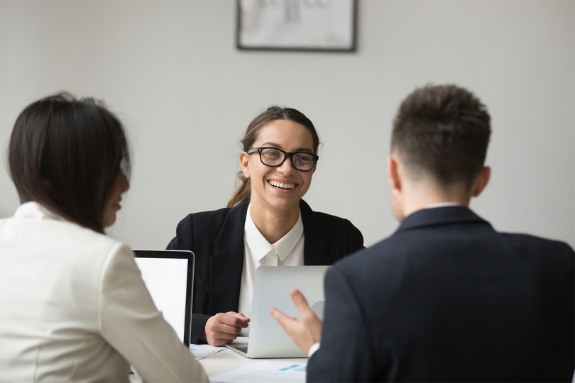 smiling-businesswoman-talking-with-subordinated-about-reports