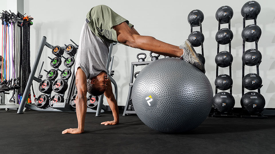 A girl performing a dumbbell press while using a stability ball