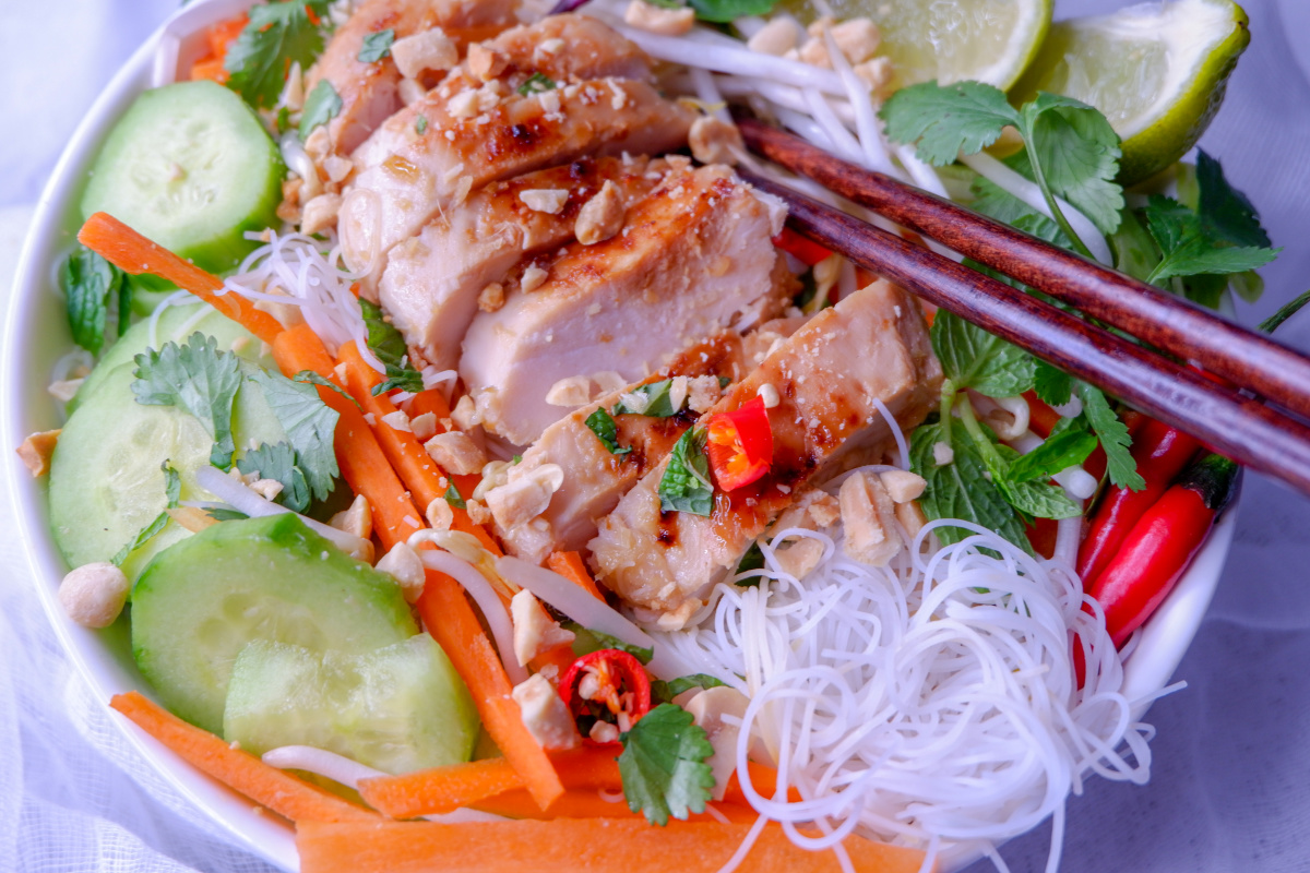 Light lemongrass chicken noodle bowl recipe that will bring you a refreshing twist to your lunch or dinner. Marinated meat, fresh vegetables and tender noodles. #healthy #lemongrass #chicken #ricenoodles #easy #mealprep #recipe #freshvegetables #Vietnamese