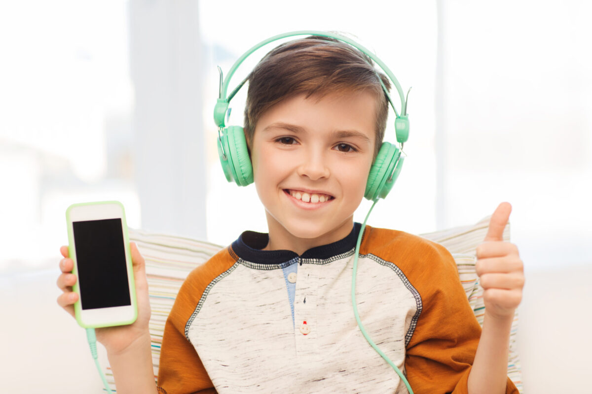 young boy with headphones on and holding a phone
