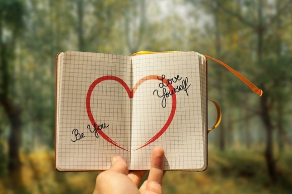 A book with a love sign and words that says be you, love yourself.