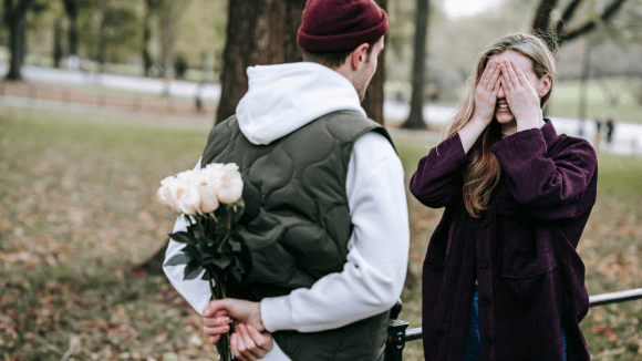 A guy giving a girl a surprise gift