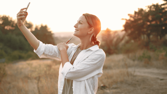 Happy woman taking selfie in nature