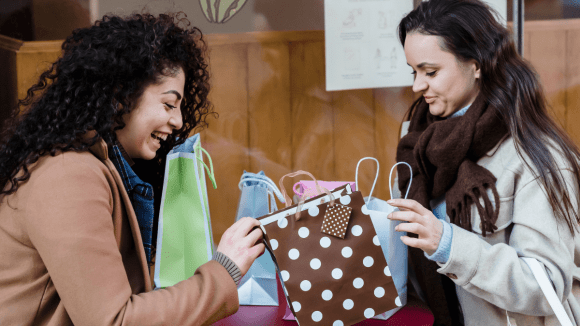 A woman smiling with gift bag on the table with her friend