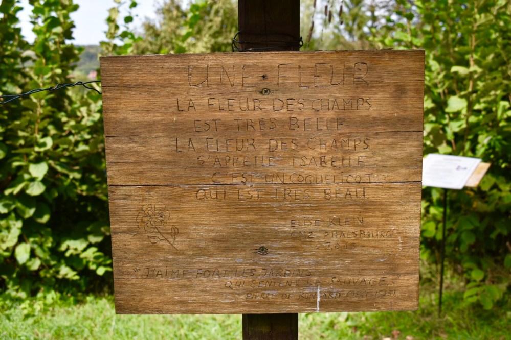 Eines von vielen Gedichten, die auf Holzschildern im Garten stehen. Dieses Gedicht ist von Elise Klein und handelt der Schönheit einer Blume.