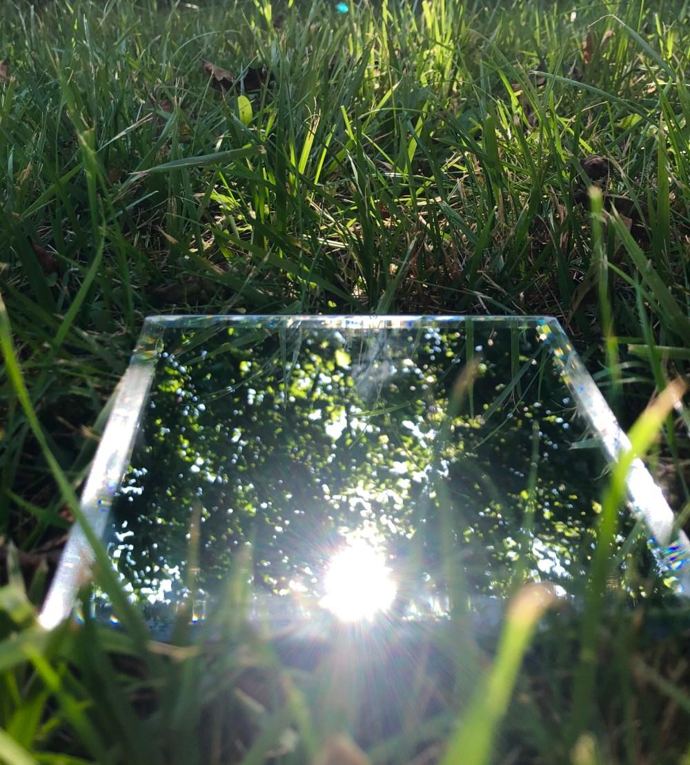 Sonnenreflexion auf einem Spiegel im Gras