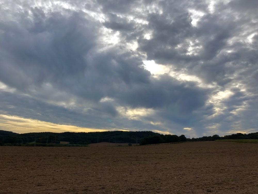 Ackerfläche unter stark bewölktem Himmel