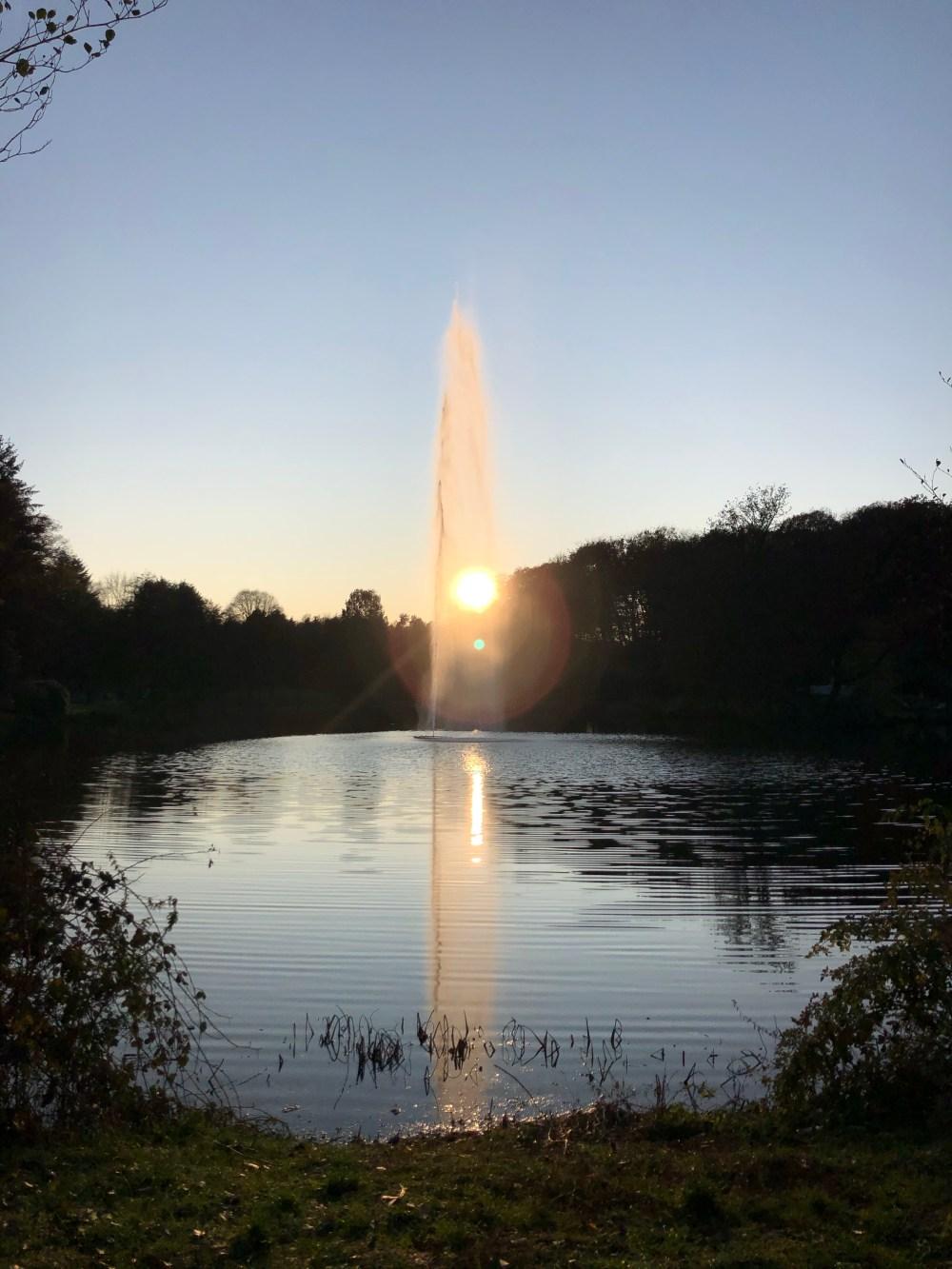 Sonnenstrahlen, die durch die Wasserfontäne hindurch strahlen