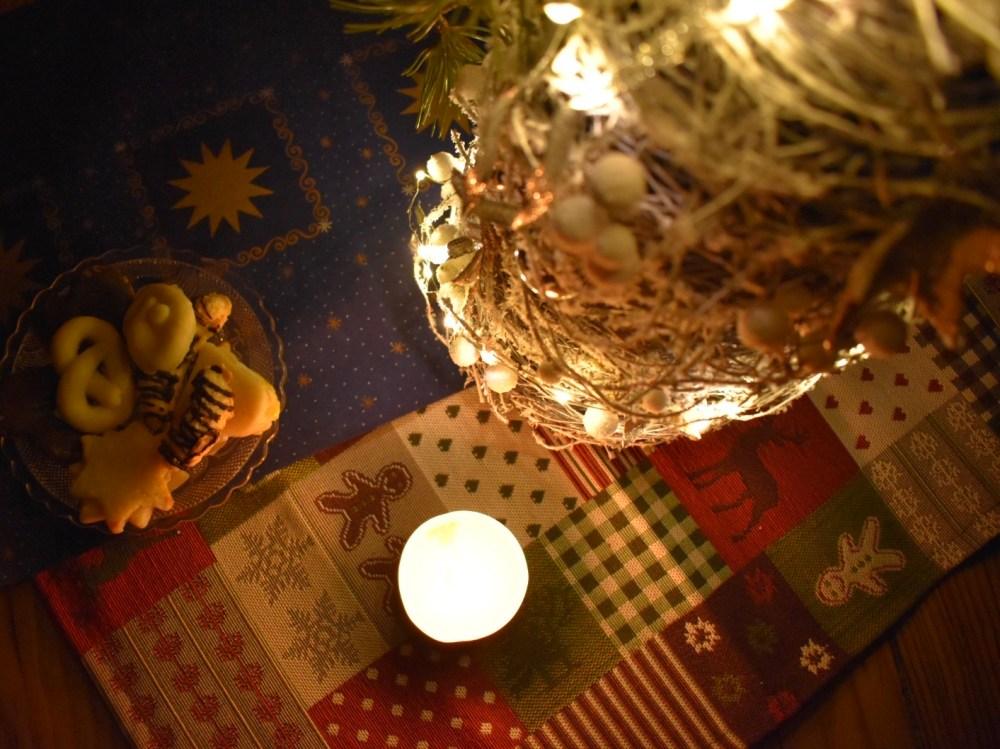 Weihnachtliches Stillleben mit Kerze, Plätzchen, Weihnachtsbaum und weihnachtlichen Tischdecken