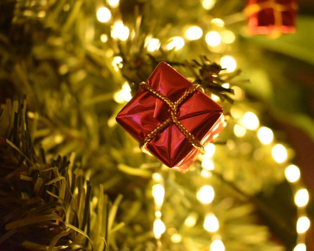 Rote Geschenkpäckchen vor Lichterketten und Tannenzweigen