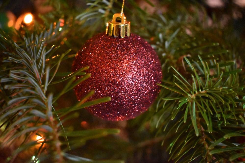 Rot glitzernde Weihnachtskugel zwischen Tannennadeln