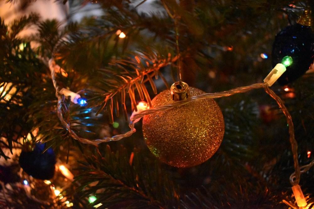 Goldene Weihnachtskugel mit einer Lichterkette im Tannenbaum