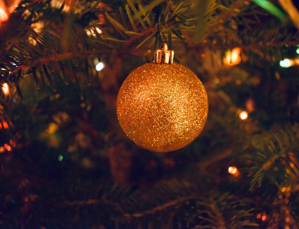 Glitzernde goldene Weihnachtskugel an einem Tannenzweig