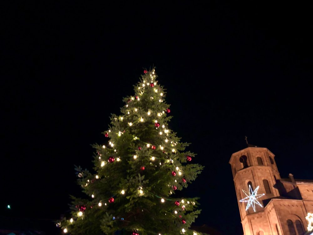 Beleuchteter Weihnachtsbaum neben einer Kirche