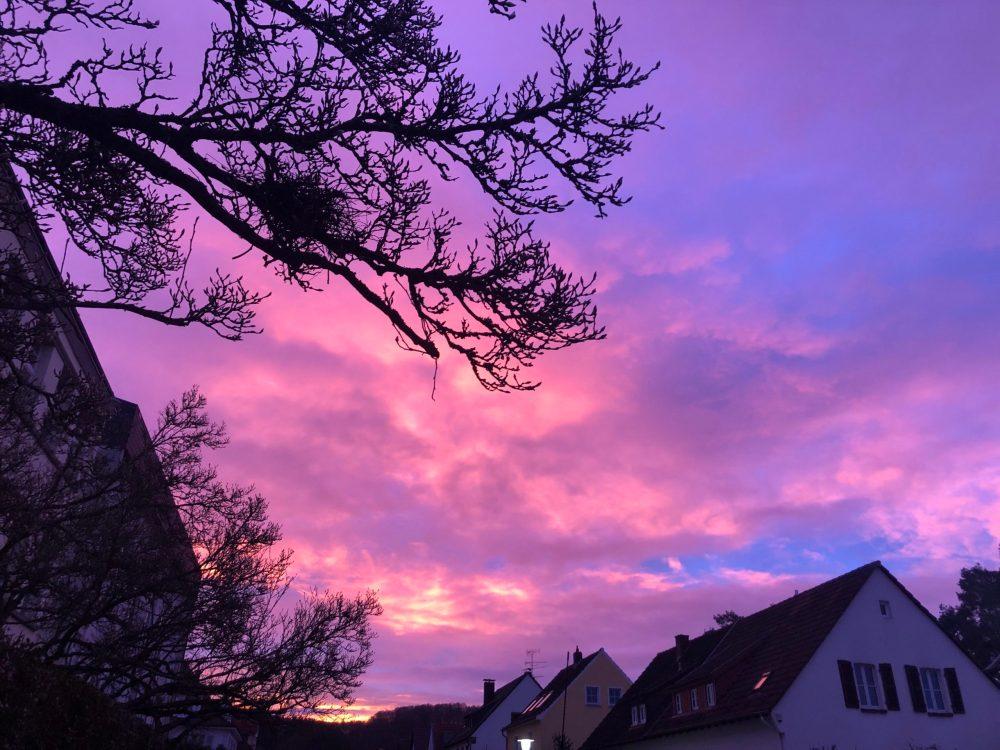 Kräftiger Sonnenaufgang über Häusern