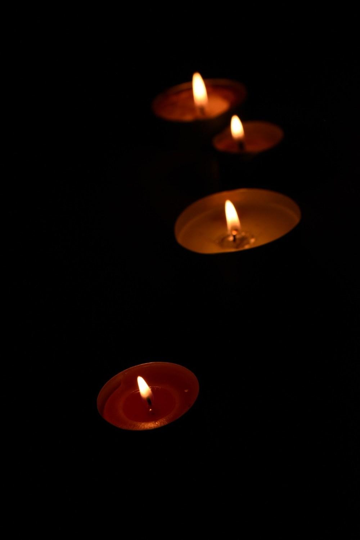 Vier brennende Kerzen im Dunkeln