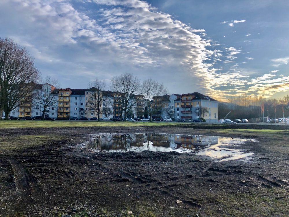 Pfütze im Schlamm vor einer Häuserreihe unter blauem Himmel mit Wolken