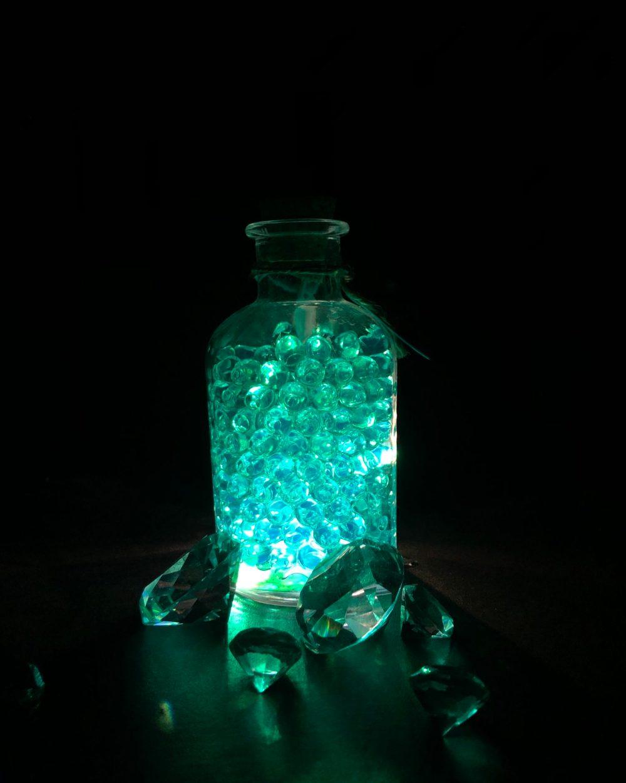 Im Dunkeln leuchtende Glasflasche vor Diamanten
