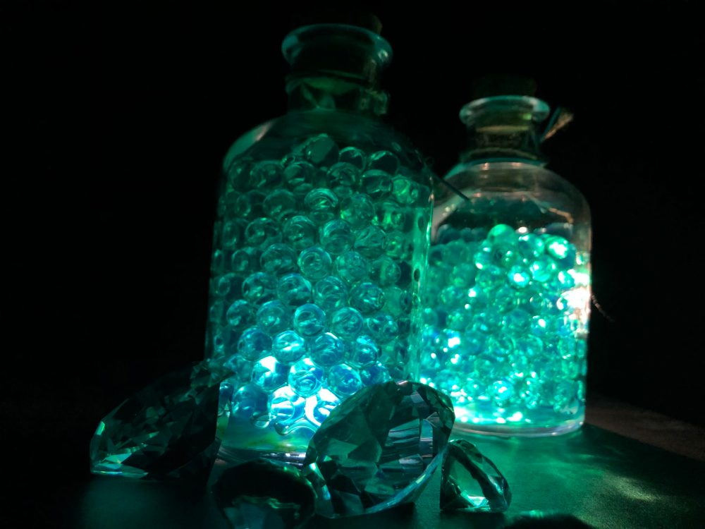 Glasdiamanten vor zwei beleuchteten Glasflaschen mit türkisfarbenen Perlen