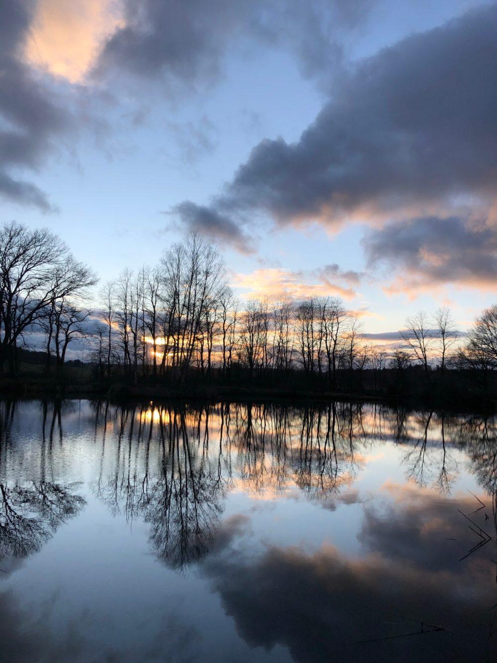 Himmel spiegelt sich auf der glatten Oberfläche des Gewässers wider