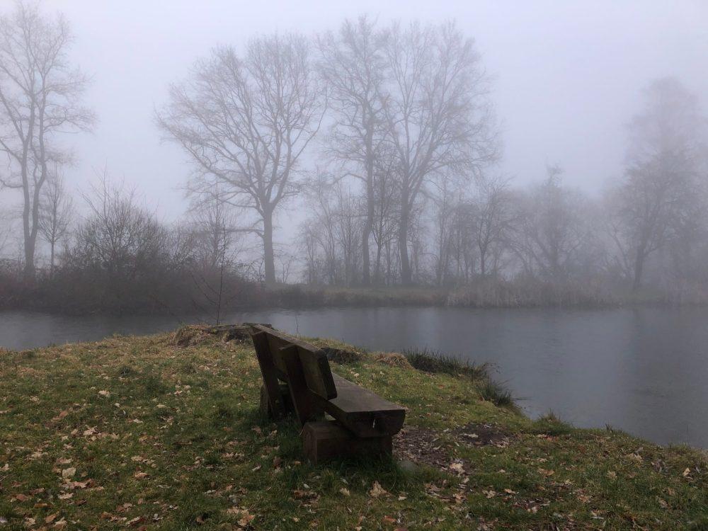 Bank vor einem Weiher im Nebelschleier