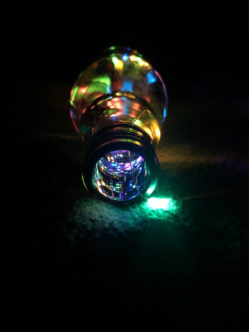 Bunte Lichteffekte in und auf einer Flaschenlampe