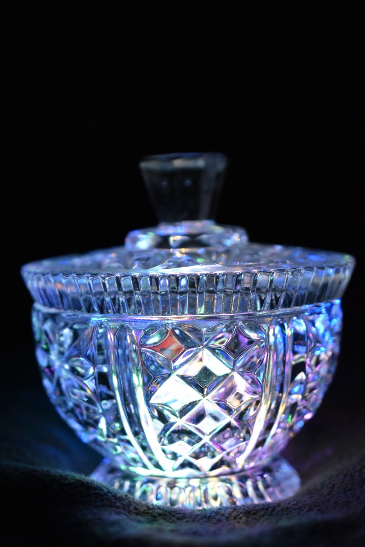 Bläulich strahlendes Kristallglas vor schwarzem Hintergrund