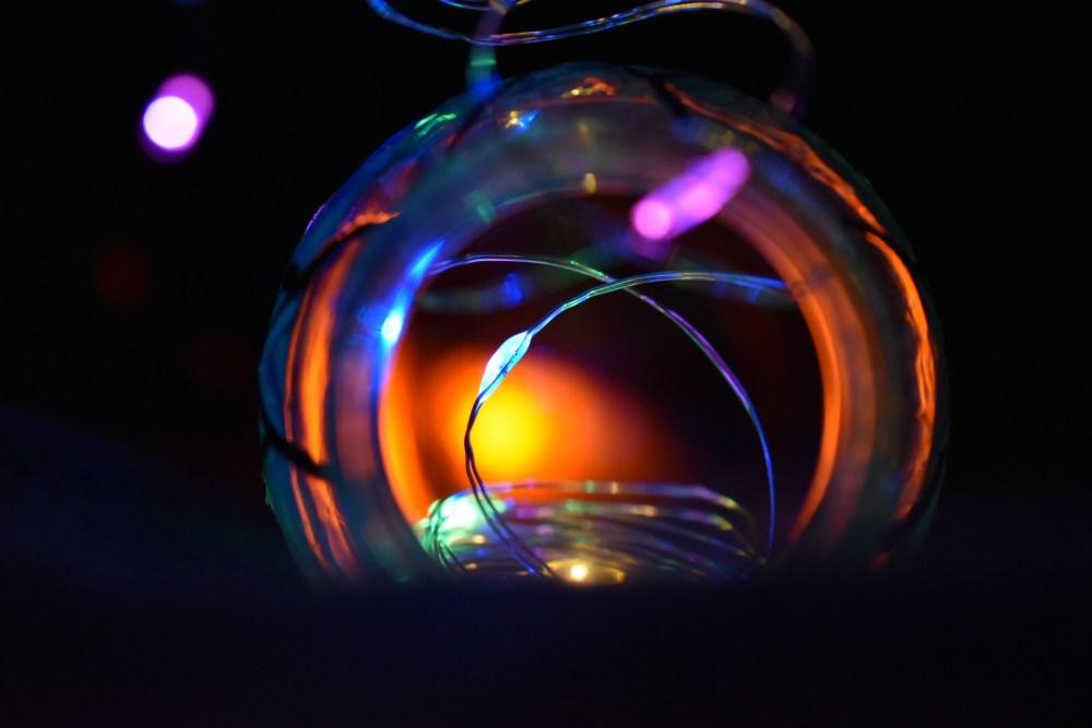 Draht mit Lichtern vor einer Glasflasche im Dunkeln