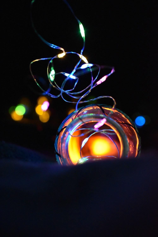 Leuchtende Lichterkette ragt aus beleuchteter Flasche heraus