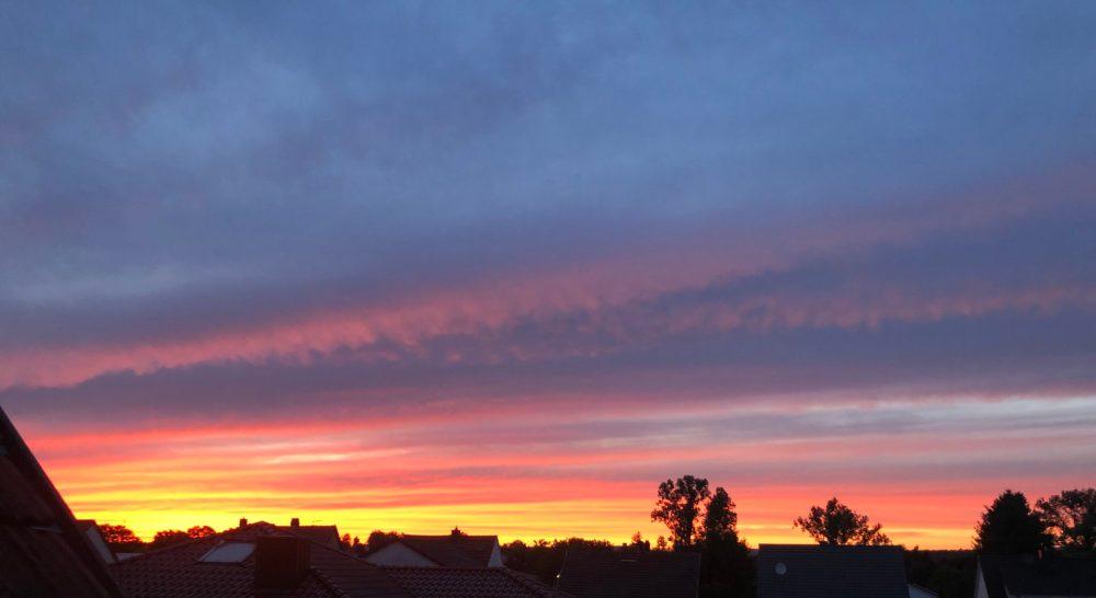 Streifenwolken bedecken die untergehende Sonne