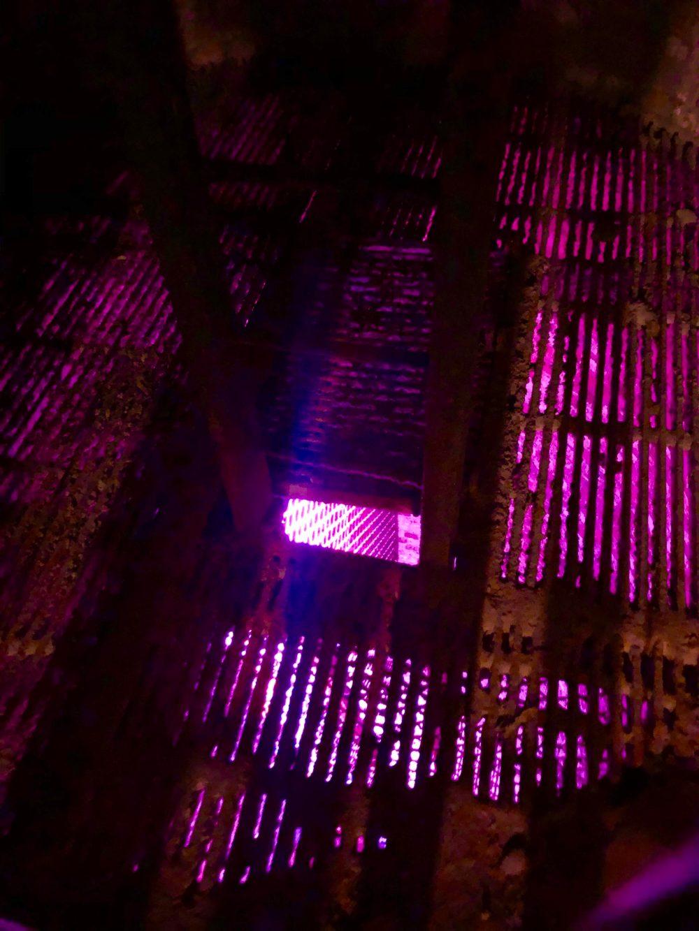 Beleuchtetes Gitter über dem 30 Meter tiefem Schacht in den Keller der Karlsberg-Brauerei
