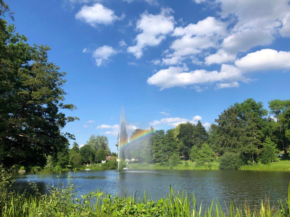 Regenbogen Reflexion durch die Wasserfontäne auf dem Furpacher Weiher