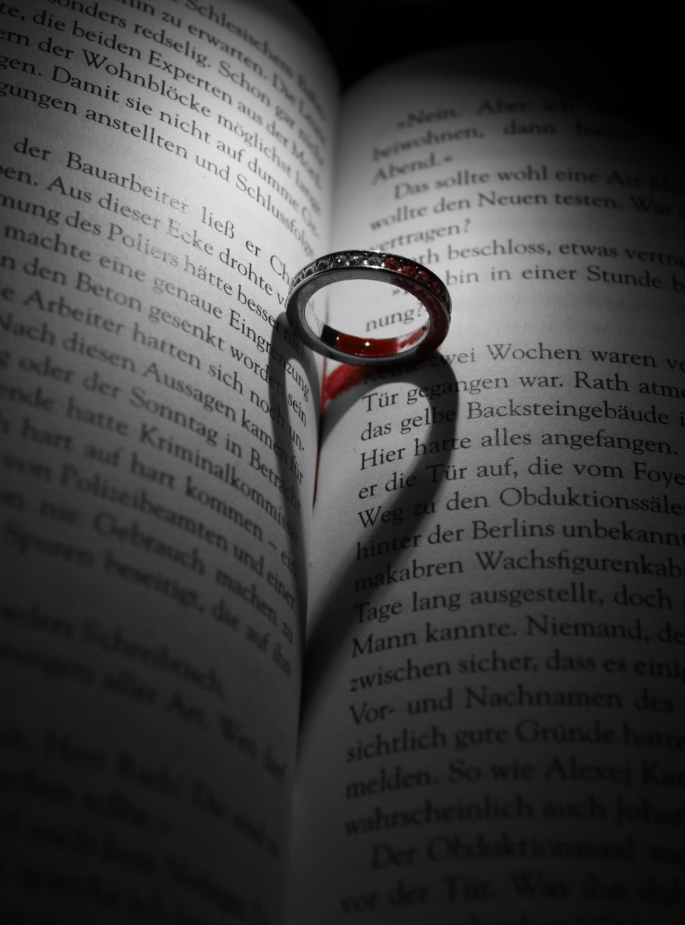 Ring mit Blut wirft Herzschatten auf ein Buch