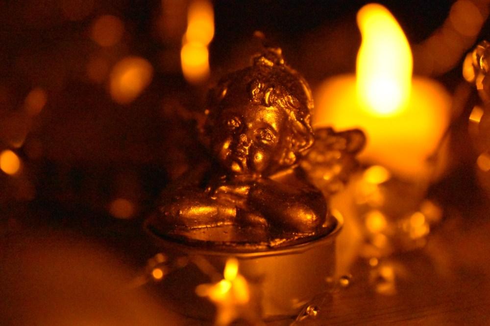 Engelkerze mit unechter Kerze im Hintergrund