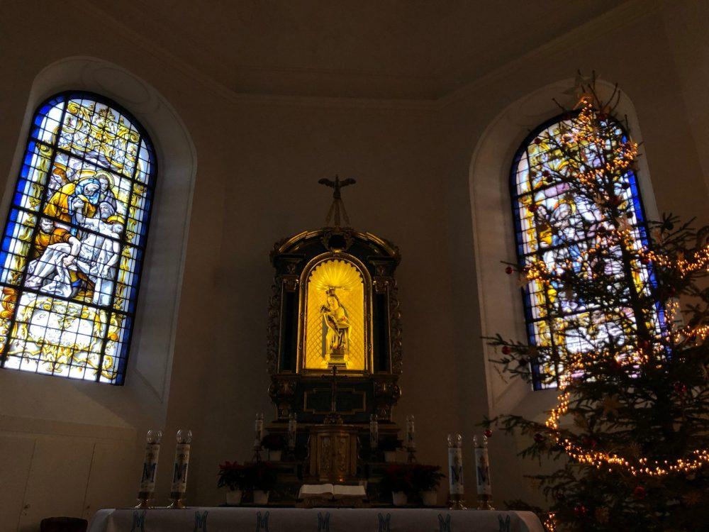Innenraum der Kapelle mit bunten Glasfenstern und Altar