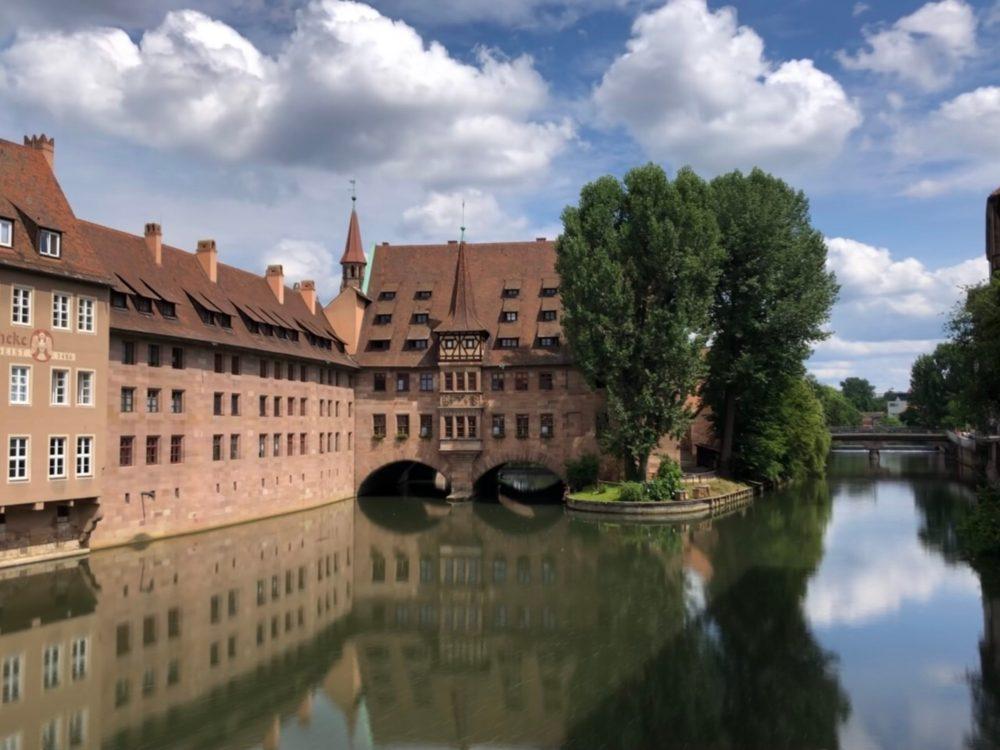Alte Gebäude auf der Insel Schütt spiegeln sich im Fluss (Langzeitbelichtung)