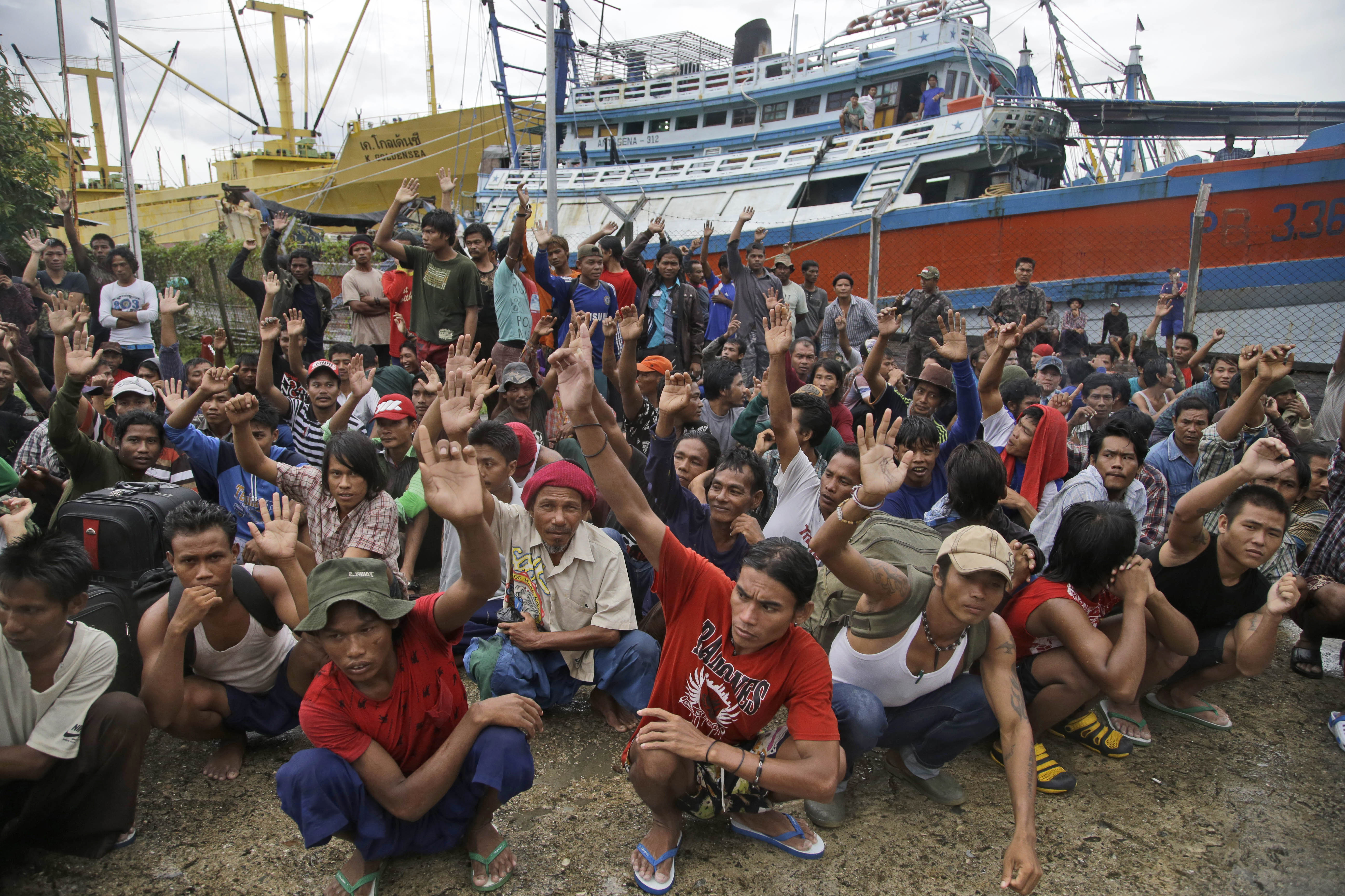 FILE - In this Friday, April 3, 2015 file photo, Burmese fishermen raise their hands as they are asked who among them wants to go home at the compound of Pusaka Benjina Resources fishing company in Benjina, Aru Islands, Indonesia. On Thursday, March 10, 2016, five Thai fishing boat captains and three Indonesians were sentenced to three years in jail for human trafficking in connection with slavery in the seafood industry. The suspects were arrested in the remote island village of Benjina in May 2015 after the abuse was revealed by The Associated Press in a report two months earlier. (AP Photo/Dita Alangkara)