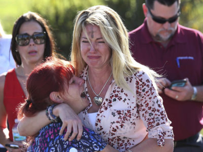 Parents wait for news after a reports of a shooting at Marjory Stoneman Douglas High School in Parkland, Florida, on Feb. 14, 2018. (AP Photo/Joel Auerbach)