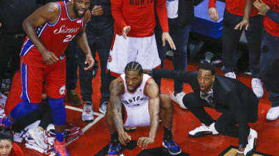 Philadelphia 76ers center Joel Embiid (21) watches from the corner as Toronto Raptors forward Kawhi Leonard (2) squats down and sticks out his tongue waiting for the ball to drop for Raptors to win. (Photo by Rick Madonik/Toronto Star)