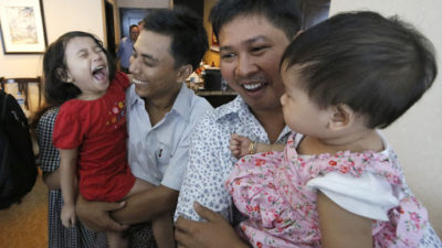 Reuters reporters Wa Lone, center right, and Kyaw Soe Oo hold their children after being freed from prison. (Ann Wang/Pool Photo via AP)