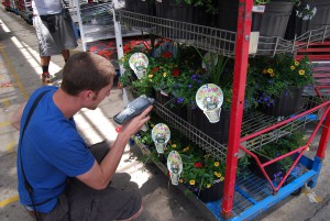 A young man knees to scan labels on flower pots that sit on a rolling shipping cart at Metrolina Greenhouses.